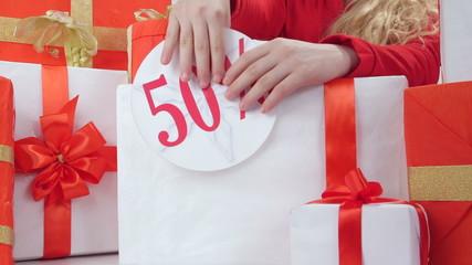 Girl sticks half price sign on red white gift boxes