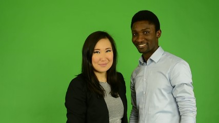 Happy multicultural couple high five and smile- green screen