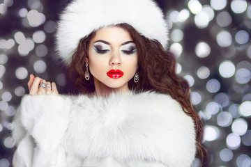 Fashion girl model posing in fur coat and white furry hat. Winte