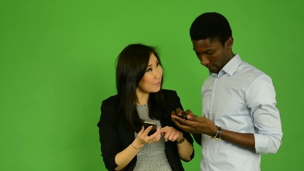 happy multicultural couple work smartphone,smile - green screen
