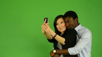happy multicultural couple take photo - green screen studio