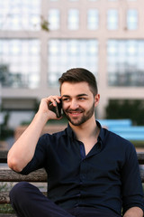 Young businessman talking on phone on a bench