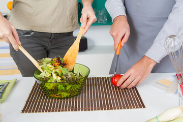 Close-up couple hands preparing salad in a bowl