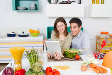 Portrait of couple looking at a tablet in a kitchen