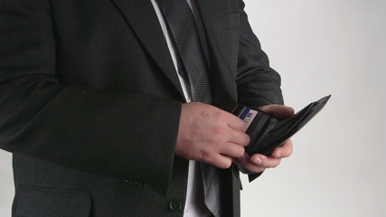 Business person takes out credit card from a leather wallet