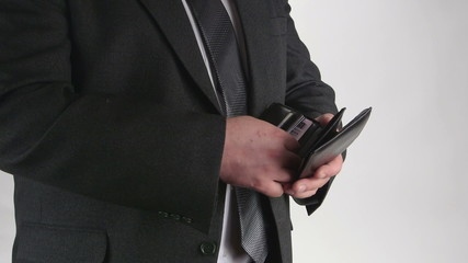 Man dressed in business suit takes out credit card from wallet