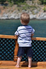 Little boy looks from the boat