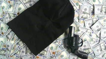 Balaclava and gun on pile of $100 american dollar banknotes