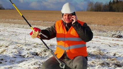 Electrical worker with cell phone near tensioner