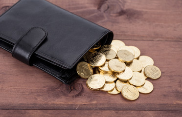 Black leather wallet with golden coins on wood background