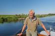 Senior man in boat on river