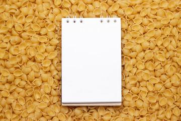 blank notepad on uncooked macaroni background