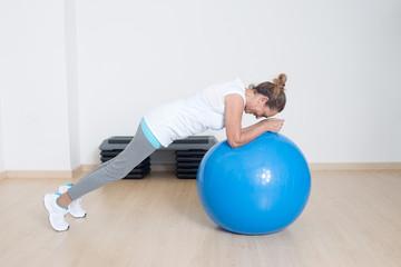 Elderly woman making exercise on fitness ball