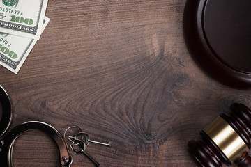 handcuffs gavel and money on wooden background