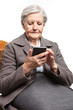 Senior woman using mobile phone while sitting on chair