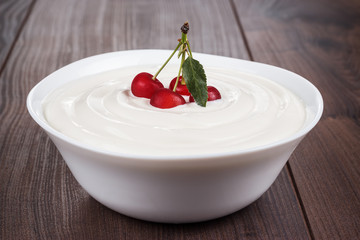 white bowl full of sour cream with some cherries