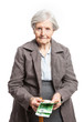 Senior woman counting money while standing over white