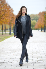 Happy woman in black coat walking autumn street