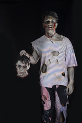 Scary male zombie holding another man's head