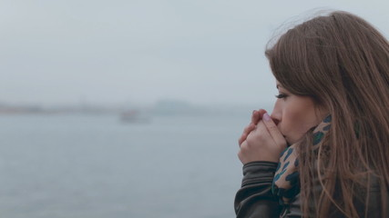 Close up of feminine girl sitting on a wooden pier near the sea