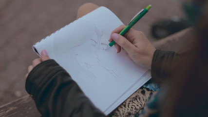 Close up of girl which drawing a picture of kissing couple on a