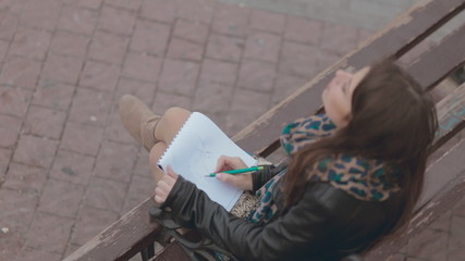 Romantic girl sitting on a bench and drawing pair of lovers in