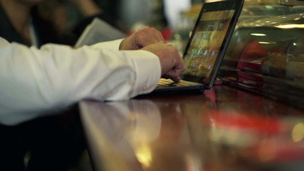 Businessman hands typing on modern laptop sitting by counter