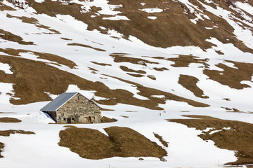 Alpine mountain landscape with cottage, snow is melting away
