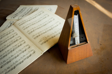 Wooden metronome sets the rhythm by swinging pendulum