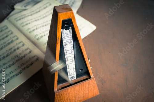 Wooden metronome sets the rhythm by swinging pendulum - 75393814