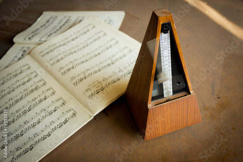Wooden metronome sets the rhythm by swinging pendulum - 75393828