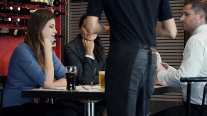 Businesspeople talking and drinking beer sitting in restaurant