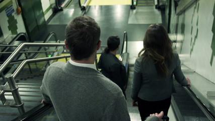 Businesspeople riding down on escalator