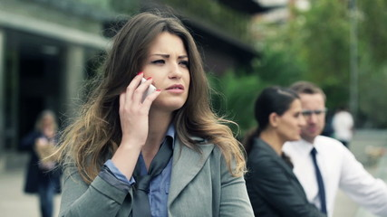 Young, pretty businesswoman talking on cellphone in the city
