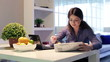 Businesswoman reading newspaper and eating breakfast at home