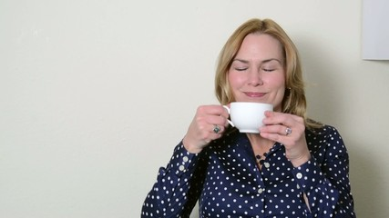 Woman walks up to coffee pot and takes a cup of coffee