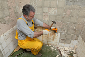 Home renovation, worker demolish tiles in a bathroom