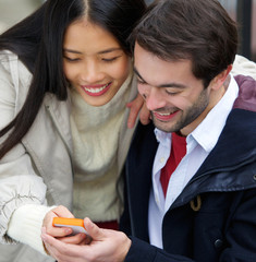Couple smiling and looking at message on mobile phone together
