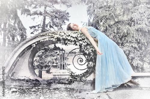 Leinwanddruck Bild Sleeping beauty in long, blue dress - winter scenery