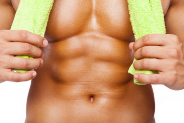Fitness man holding a towel and showing six pack abs