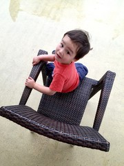 Cute young mixed race boy sitting in chair.