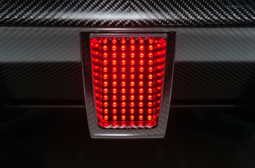 Rear light of powerful sport car. Active red stop signal.