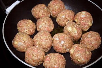 Uncooked homemade meatballs in skillet ready for cooking
