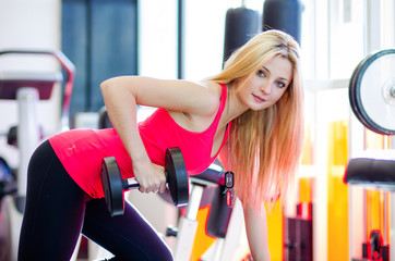 young woman holding weights and doing fitness indoor