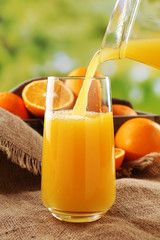 Pouring orange juice from glass carafe,
