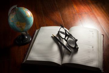 Globe with eyeglasses,pen and plan book