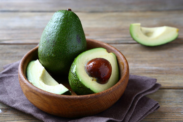 Fresh avocado in a wooden bowl