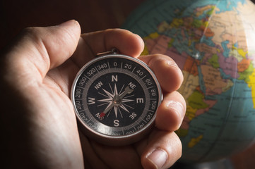 Compass in human hand with globe.