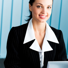 Happy businesswoman working with laptop at office