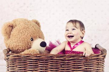 Beautiful little girl with big teddy bear in the wicker basket